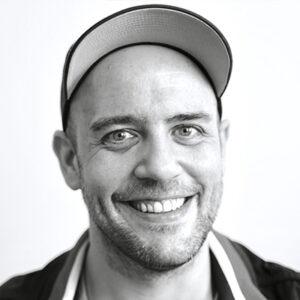 Mann mit Kappe lächelt in Kamera