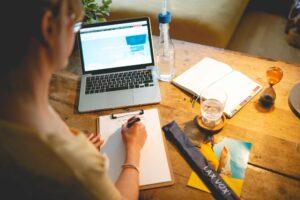 Frau sitzt an einem Schreibtisch vor einem Laptop und lernt die Hintergründe von LAX VOX®