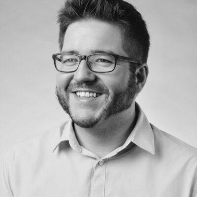 Mann mit kurzen Haaren und Brille lächelt